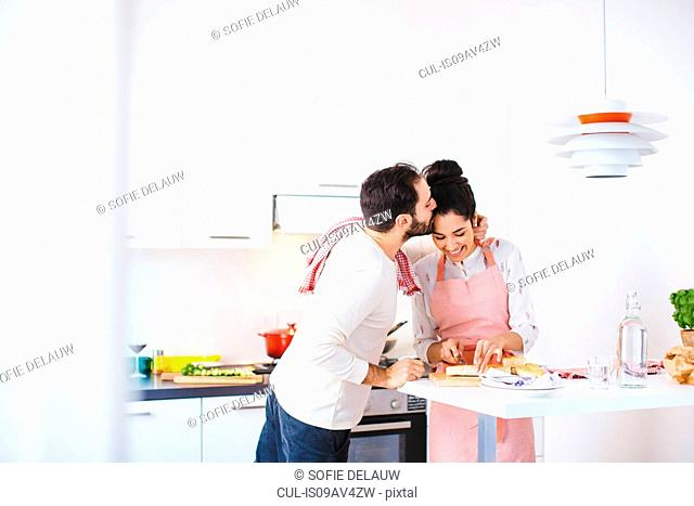 Romantic young couple in kitchen preparing food
