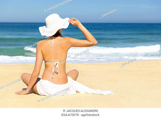woman with sun hut sits in front of the sea