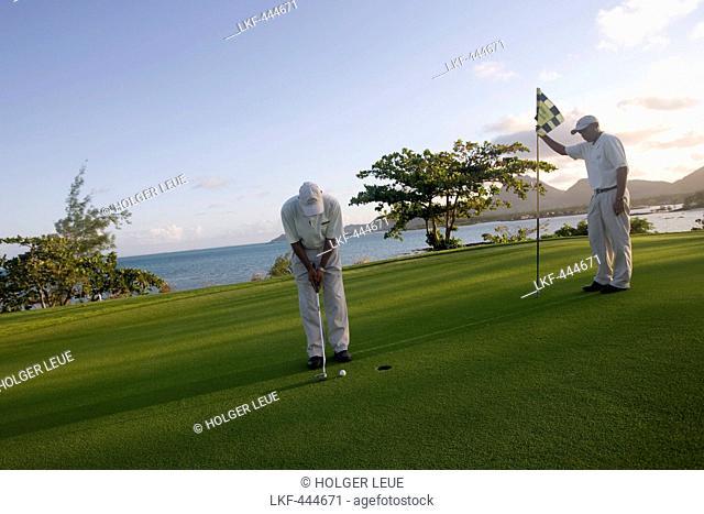 Golfer puting on the Green of Hole 11: Round the Bend at Le Touessrok Golf Course, Ile aux Cerfs Island, near Trou d'Eau Douce, Flacq District, Mauritius