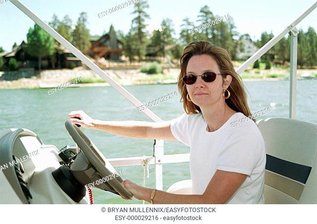 34 year old woman driving pontoon boat on Big Bear Lake. California, USA