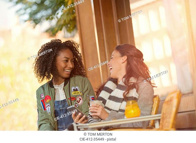Laughing young women friends with cell phone at urban sidewalk cafe