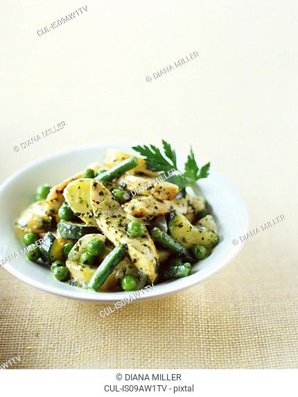 Chicken, peas, potatoes with herbs and butter in bowl