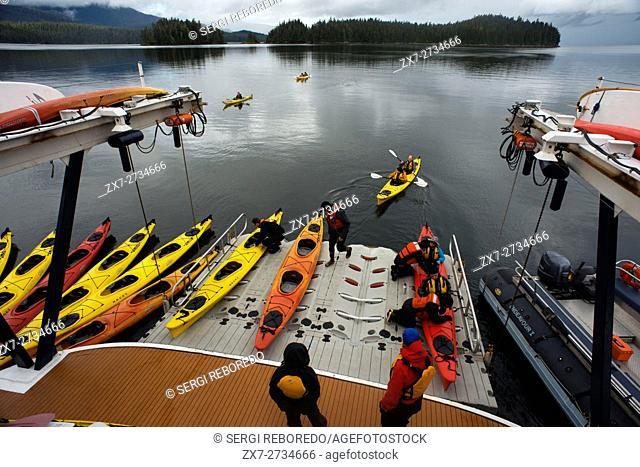People getting into sea kayaks on loading dock cruise ship Safari Endeavour near Reid Glacier in Glacier Bay National Park
