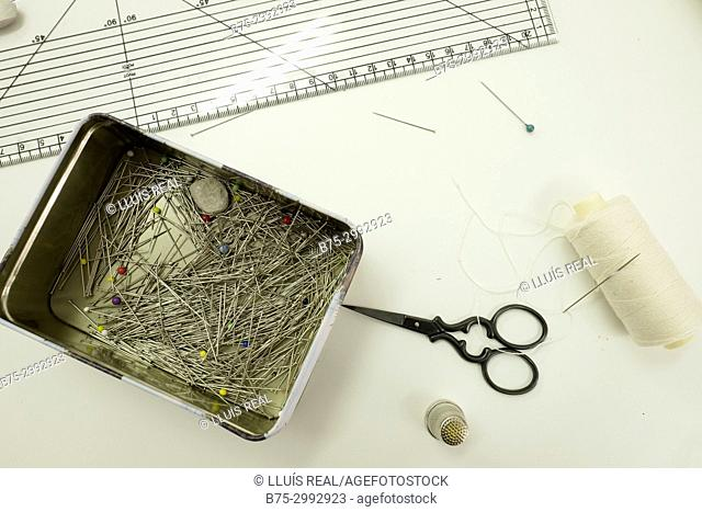 Close-up of a tailor's table with a ruler, scissors, thimble, box with needles and a thread spool with a needle inside it