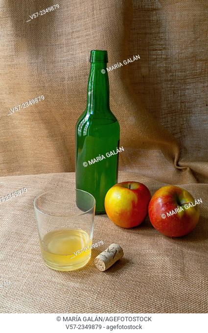 Asturian still life: glass of cider, bottle, cork and two apples. Asturias, Spain