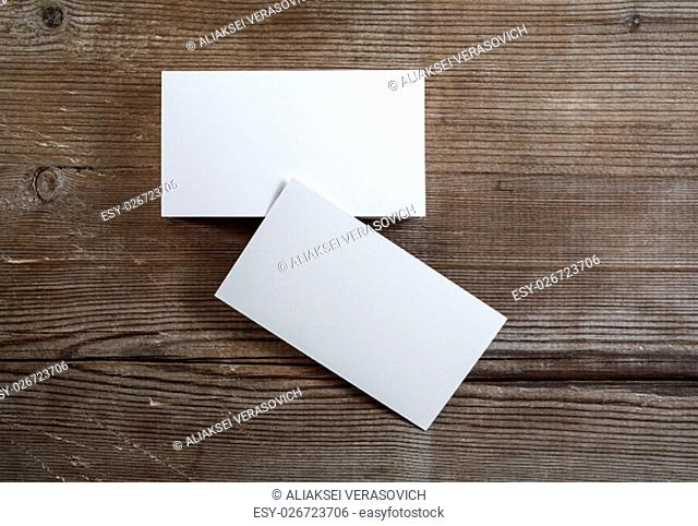 Photo of blank business cards on a dark wooden background. Mock-up for branding identity. Top view