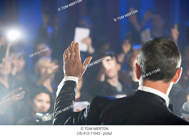 Rear view of male celebrity waving to paparazzi
