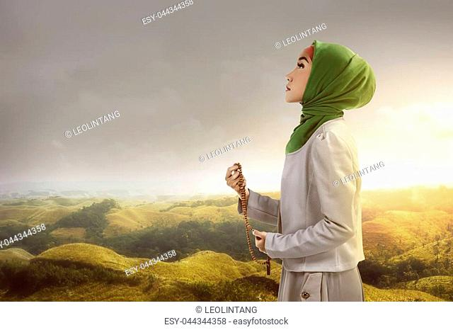 Young muslim woman holding prayer beads standing on mountain