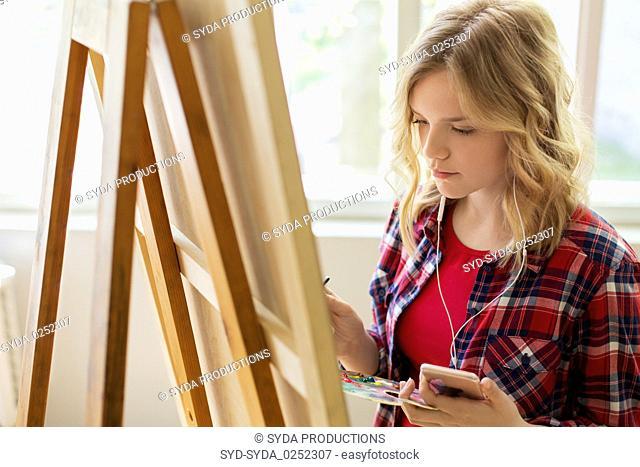 teenage girl with smartphone at art school studio
