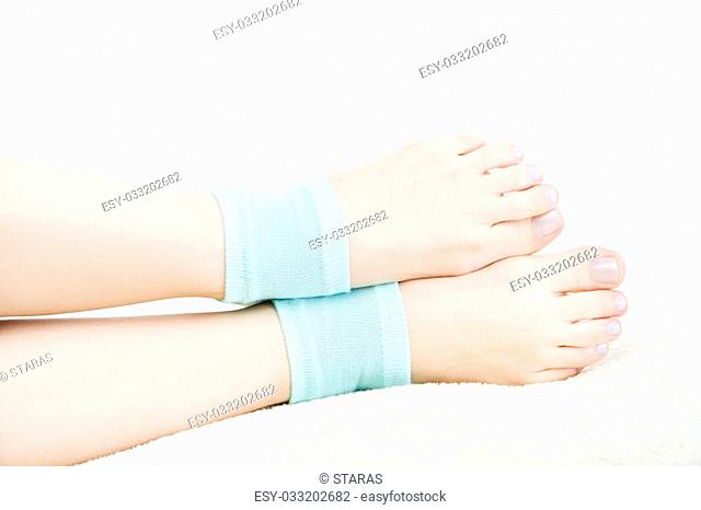 Beautiful female legs in blue socks isolated on white background. Foot care