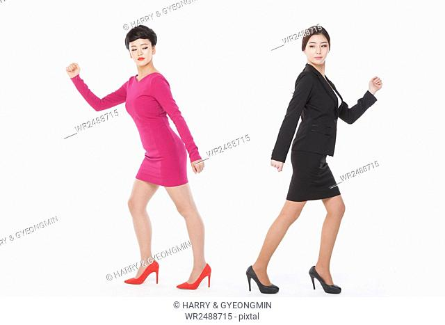 Two young business women walking to different directions looking aside