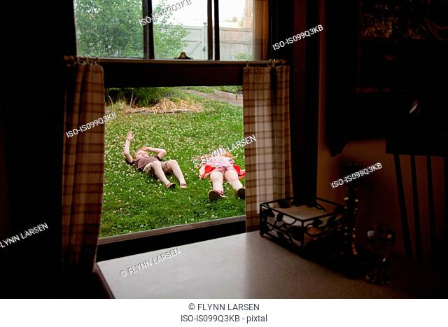 View through window of boy and and girl lying in garden
