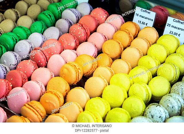 Close up of colourful macaroons in a bakeries display case; Dinan, Brittany, France
