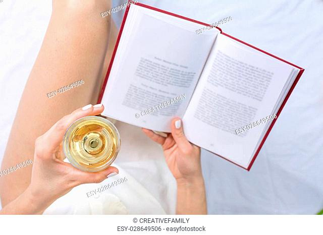 Woman having a glass of white wine in bed