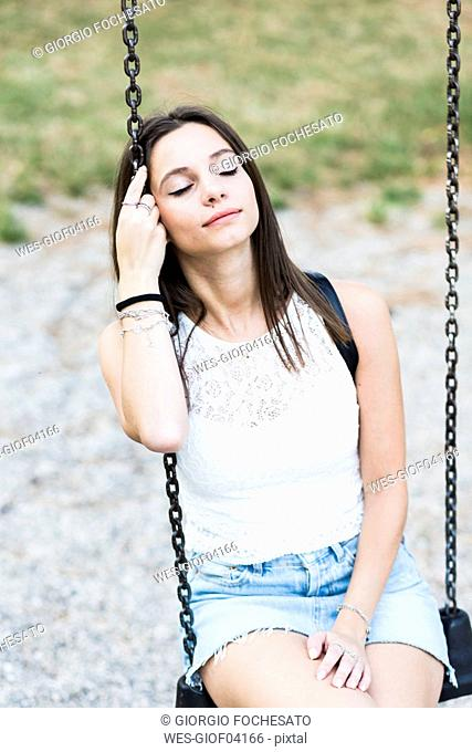Young woman with closed eyes sitting on a swing on a playground
