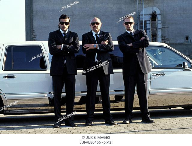 Three men in suits with arms crossed in front of limousine