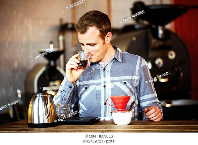 Specialist coffee shop. A man brewing coffee using a filter paper, and drinking it