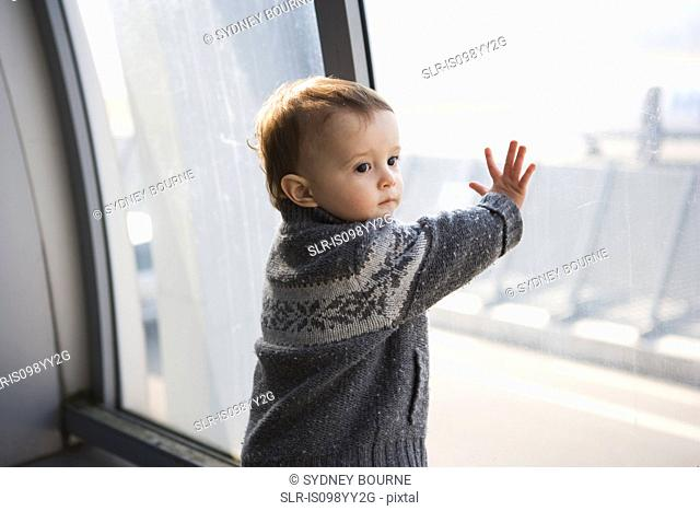 Boy touching airport window