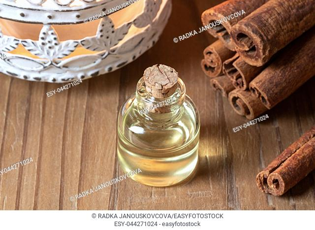 A bottle of essential oil with cinnamon sticks