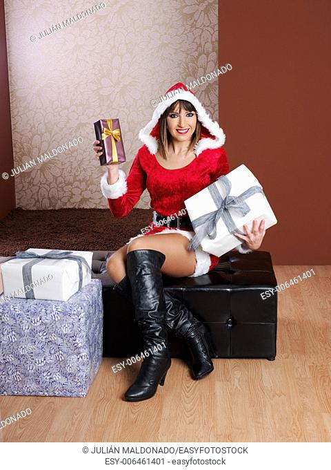 Young woman dressed in Mama Claus showing some gifts