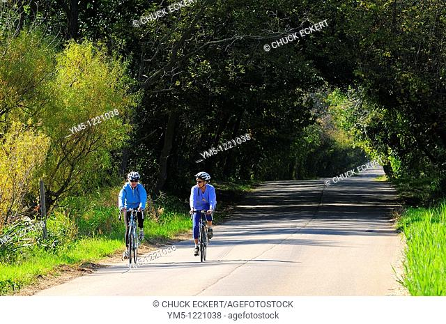 Two Women bicycling on country road