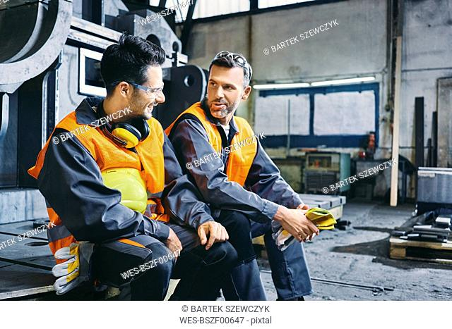 Two men wearing protective workwear talking during break in factory
