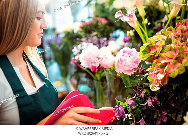Female florist pouring water in flower vase