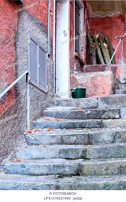 Detail of steep uneven stone stairway up narrow alley with walls of houses painted red/orange in typical evocative style of Northern Italy