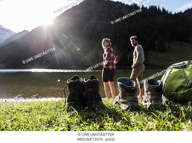 Austria, Tyrol, hiking shoes and couple refreshing in mountain lake
