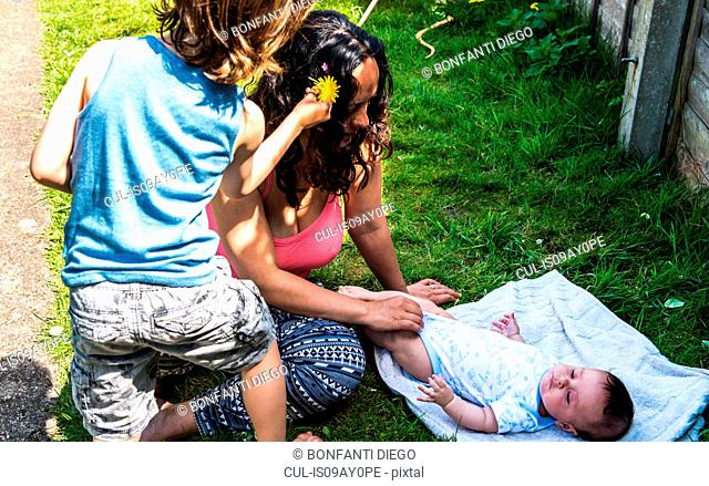 Boy playing with mother and baby brother in garden