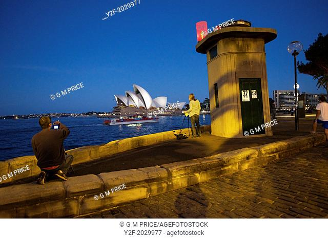 photographers and strollers with a view across Sydney Cove to the Opera House at dusk
