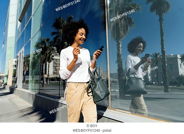 Young casual businesswoman using smartphone in the city