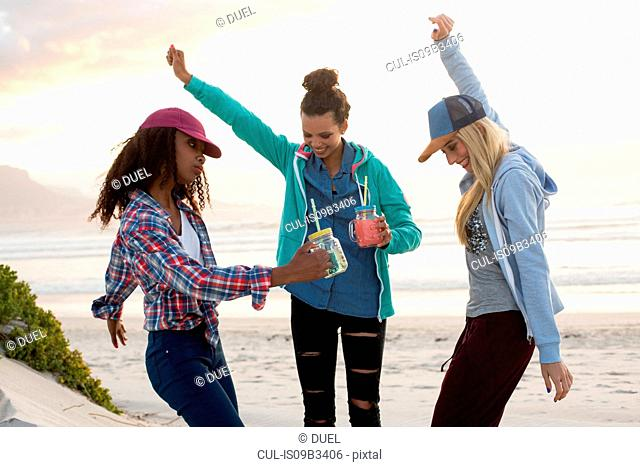 Three young female friends dancing together on beach, Cape Town, Western Cape, South Africa