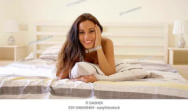 Single young adult woman with cheerful expression laying down on bed with hand on side of face in white room