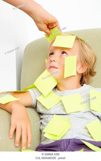 Hand sticking adhesive notes on boy