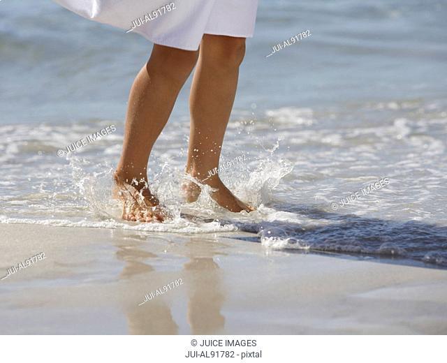 Girl walking in surf at beach