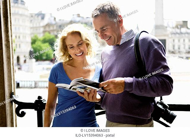 A middle-aged couple standing by Trafalgar Square, looking at a guidebook