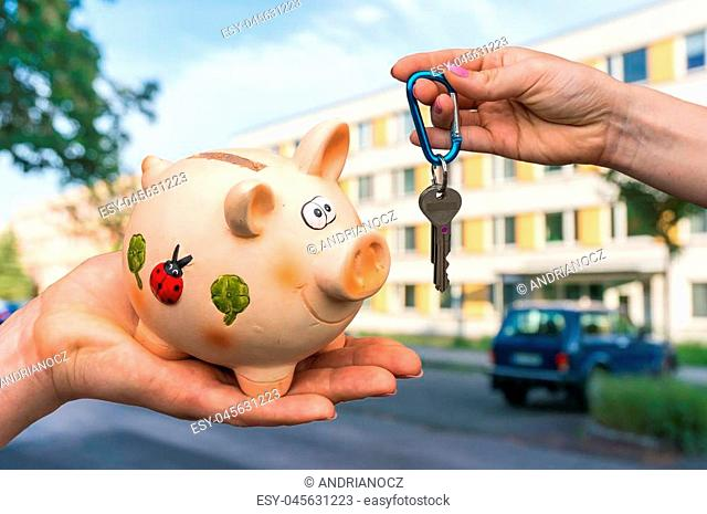 Real estate agent giving home keys to a new property owner, who is paying all saving money from piggy bank on blurred background