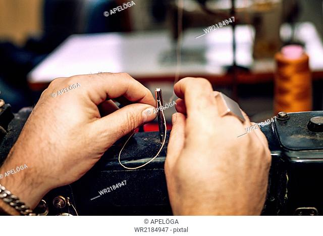 Cropped image of worker's hands inserting thread before manufacturing in factory