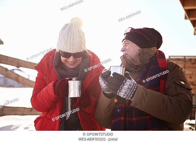 Happy mature couple with hot drinks outdoors at mountain hut in winter