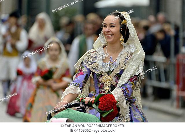 Fallas festival, young woman in a traditional costume during the parade in the Plaza de la Virgen de los Desamparados, Valencia, Spain