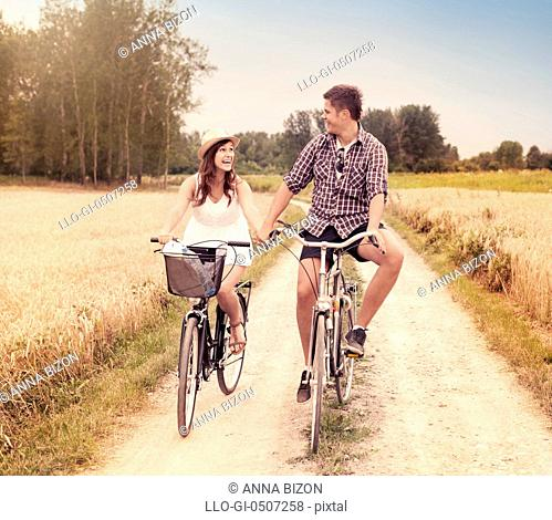 Happy couple cycling outdoors in summer, Debica, Poland