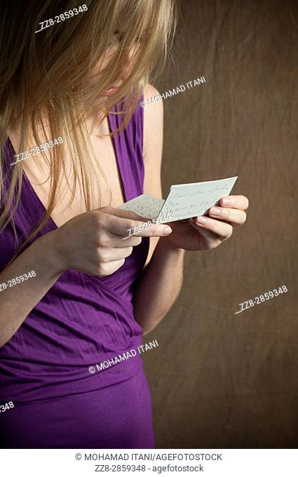 Close up of a young blond woman reading a letter