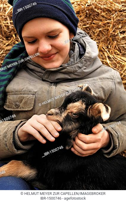 Ten-year-old girl sitting on straw embracing a goat kid on an organic farm, Othenstorf, Mecklenburg-Western Pomerania, Germany, Europe
