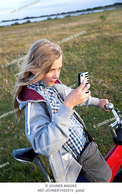 Girl on bike taking picture with her cell phone, Sweden