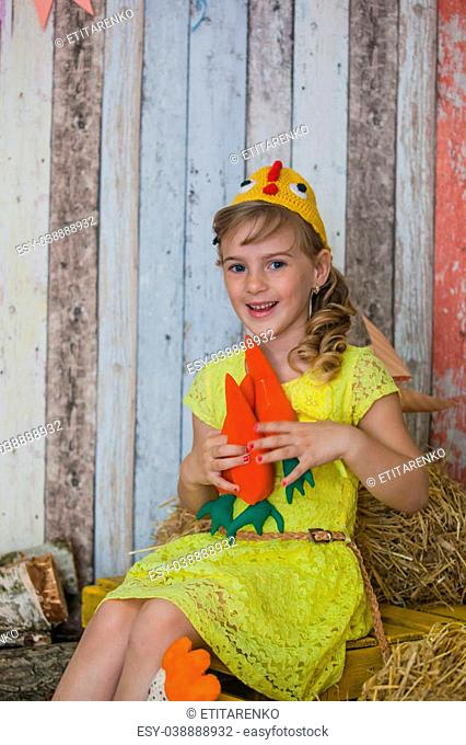 beautiful girl in the yellow dress, playing with a carrot