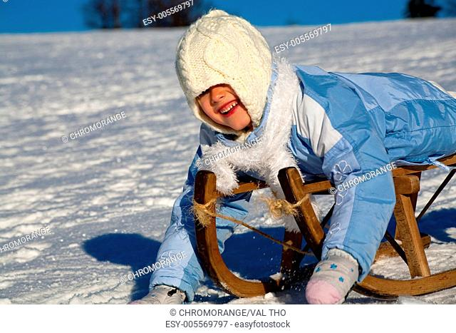 winter activities a girl sledding downhill
