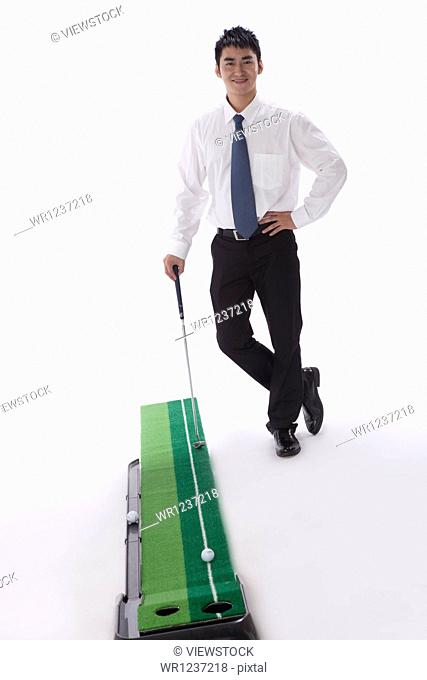 Young businessman playing golf