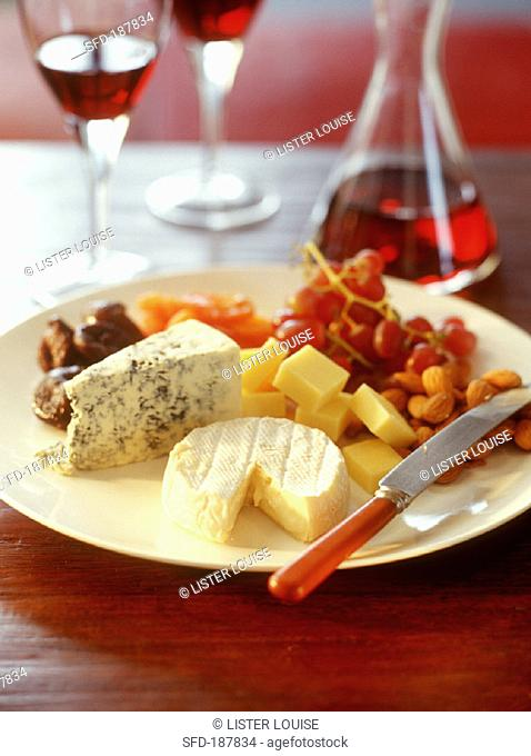 Plate of cheese with almonds and grapes