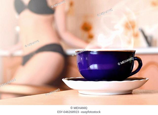 Dark blue cup of hot tea with steam on a white saucer. On blurred background girl in black lingerie near a kitchen counter